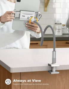 a man using goose neck tablet holder clamped on kitchen table