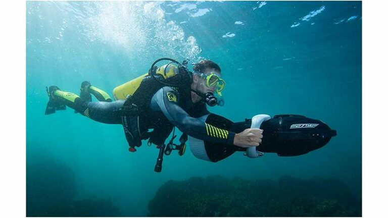 a man using underwater scooter in the ocean diving